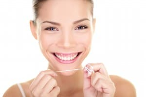 Dental flush - woman flossing teeth smiling happy with perfect t